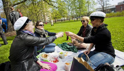 """Christine Maksimow, Varvara Teider, Pasi Perkiö ja Kerttu Kotakorpi kippistivät positiiviselle isänmaallisuudelle. Floran päivä oli heidän ensimmäisensä. """"Tilaisuus viettää piknikkiä pitää käyttää aina hyväksi"""", Teider sanoi. Auringon tultua esiin puistoon saapui lisää porukkaa, ja Mariskan ääni täytti Arabianrannan."""