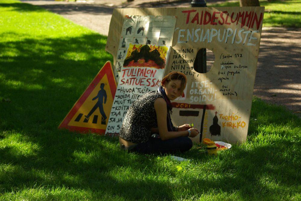 Taideslummissa on opasteita, kieltotauluja ja infokylttejä. Aktivistit toivovat saavansa lahjoituksena osan julisteisiin, taiteiseen ja koristeluun kuluvasta maalista. Kuva: Sami Moilanen.